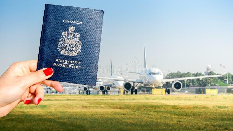Compuesto de Digitaces de sostener un pasaporte canadiense con una fila de aeroplanos comerciales en el carreteo en la pista de d fotografía de archivo libre de regalías