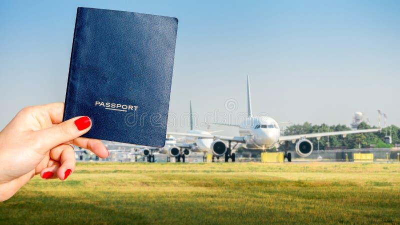 Compuesto de Digitaces de sostener un pasaporte genérico con una fila de aeroplanos comerciales en el carreteo en la pista de des imagen de archivo libre de regalías