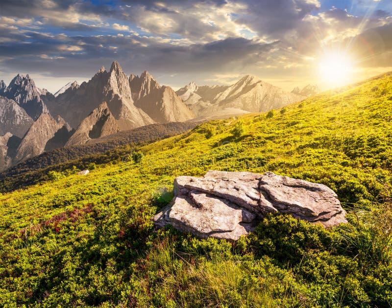 Compuesto del prado en montañas rocosas en la puesta del sol foto de archivo