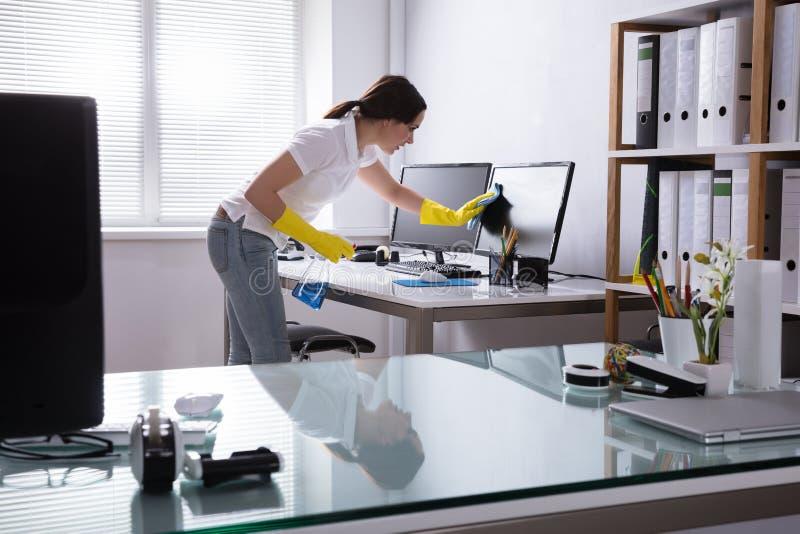 Computador da limpeza da mulher no escritório imagem de stock