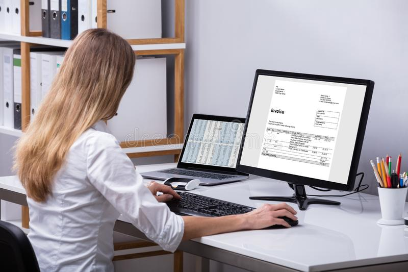 Computador de Checking Invoice On da mulher de negócios imagem de stock
