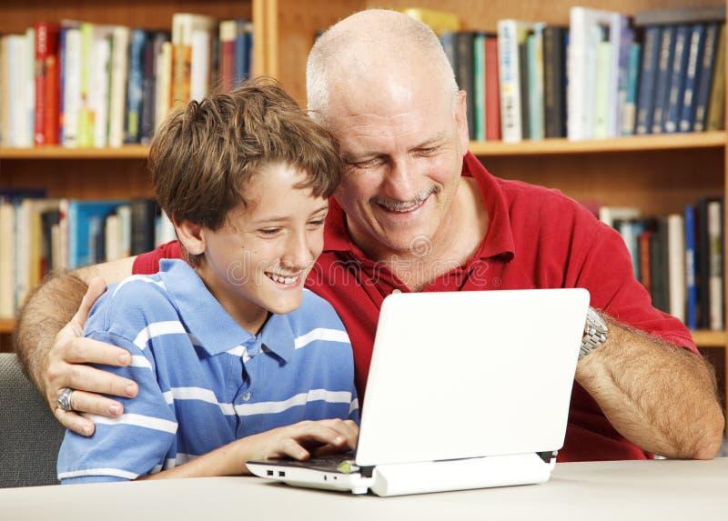 Computador de Netbook do uso do pai e do filho foto de stock