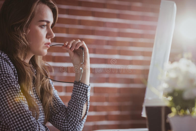 Computador de observação da mulher de negócios pensativa do moderno foto de stock