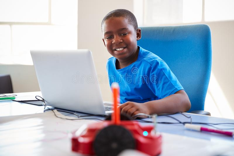 Computador de In After School do estudante masculino que codifica a classe que aprende programar o veículo do robô fotografia de stock
