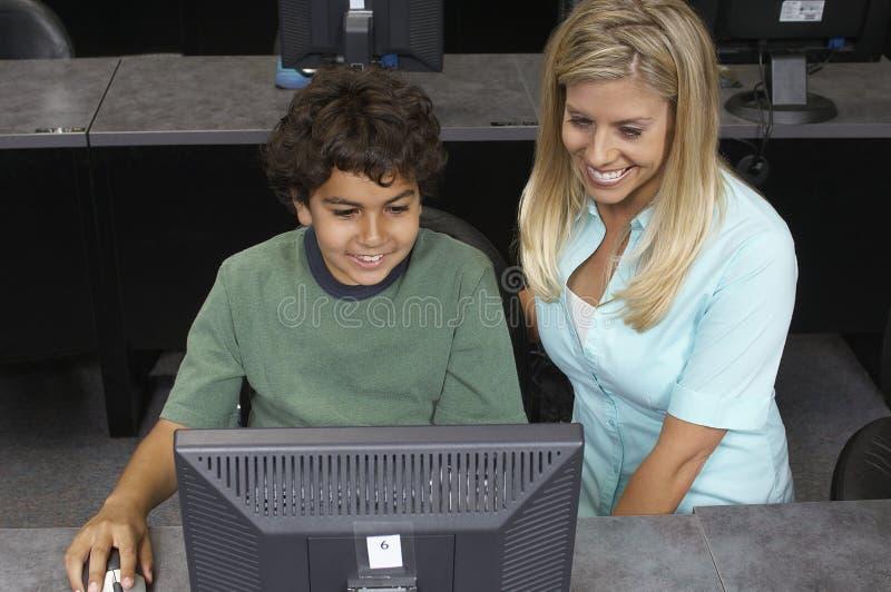 Computador de And Teacher Using do estudante masculino imagens de stock