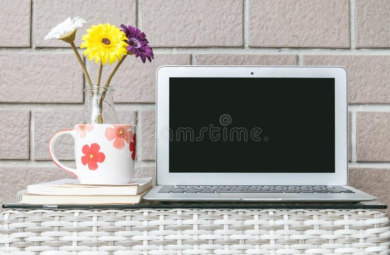 Computador do close up na tabela de madeira borrada do weave e fundo marrom da textura da parede de tijolo, interior bonito do lu fotografia de stock royalty free