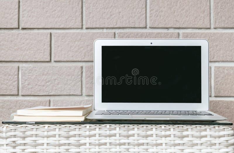 Computador do close up na tabela de madeira borrada do weave e fundo marrom da textura da parede de tijolo, interior bonito do lu foto de stock
