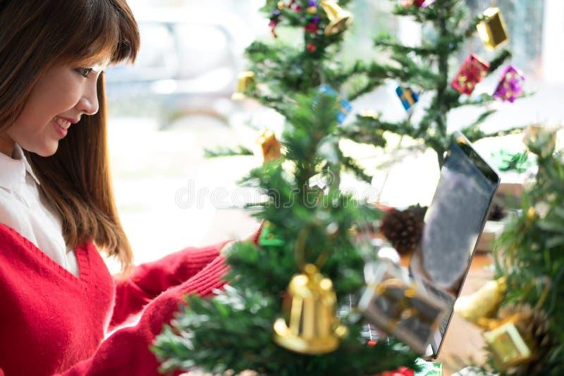 Computador do uso da mulher em casa menina com a árvore do xmas no HOL do Natal fotos de stock