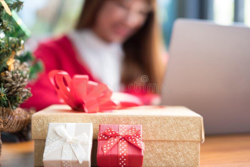 Computador do uso da mulher em casa menina com a caixa do presente do presente para chris foto de stock