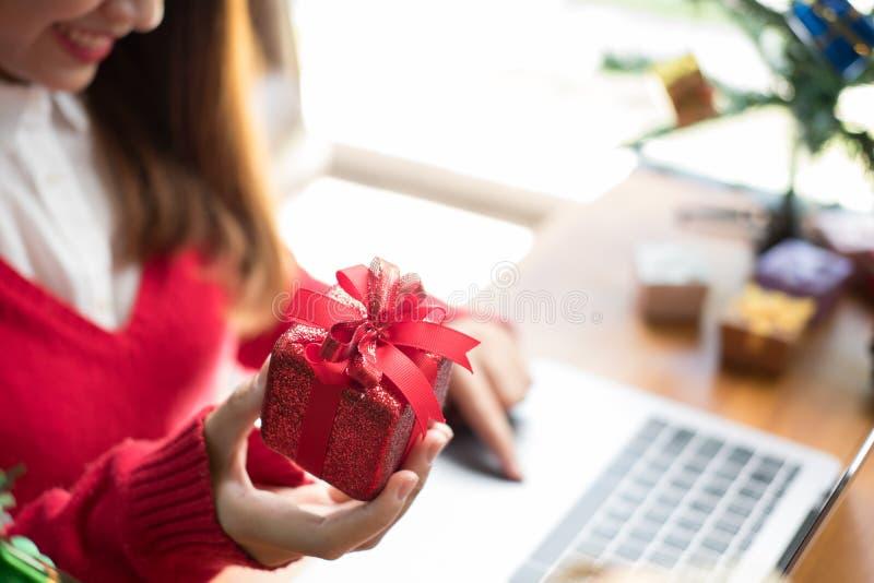 Computador do uso da mulher em casa menina com a caixa do presente do presente para chris fotos de stock