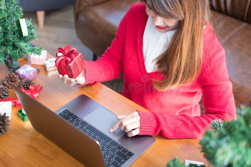 Computador do uso da mulher em casa menina com a caixa do presente do presente para chris foto de stock royalty free