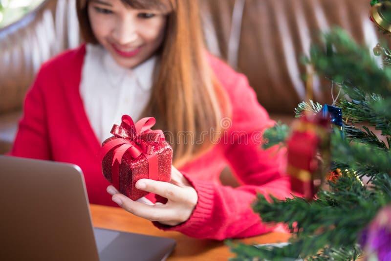 Computador do uso da mulher em casa menina com a caixa do presente do presente para chris fotografia de stock royalty free