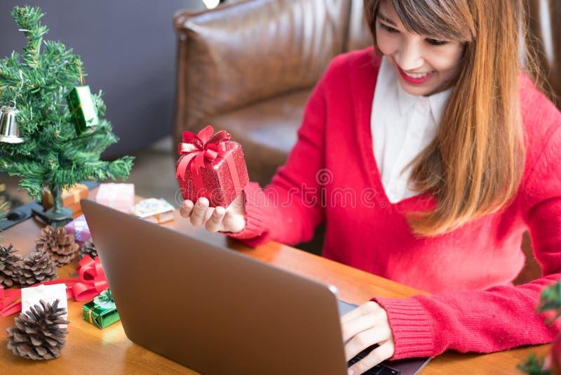 Computador do uso da mulher em casa menina com a caixa do presente do presente para chris fotos de stock royalty free