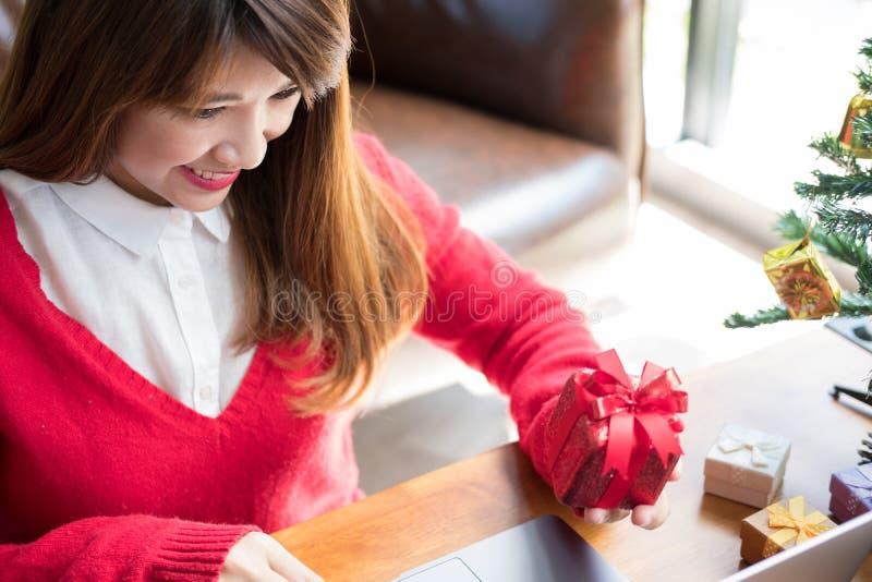 Computador do uso da mulher em casa menina com a caixa do presente do presente para chris imagem de stock royalty free