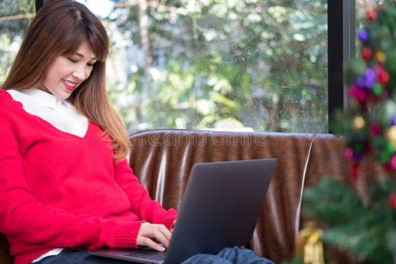 Computador do uso da mulher em casa a menina senta-se no sofá perto da árvore de Natal imagens de stock