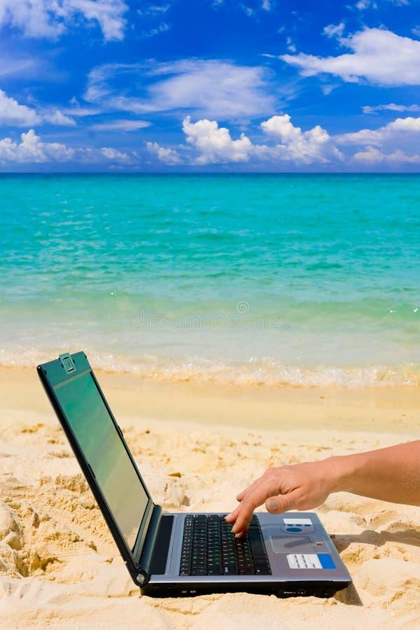 Computador e mão na praia imagens de stock