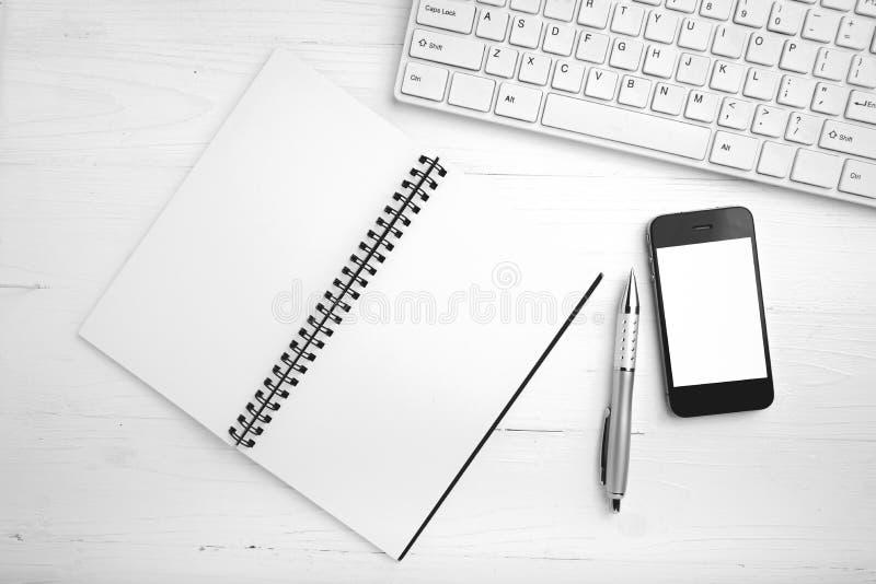 Computador e telefone celular com o colo preto e branco do caderno e da pena foto de stock