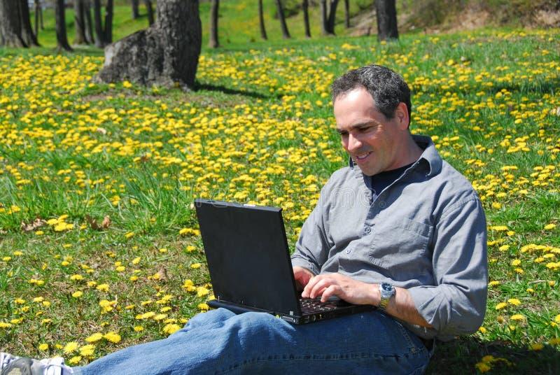 Computador exterior do trabalho do homem fotos de stock royalty free