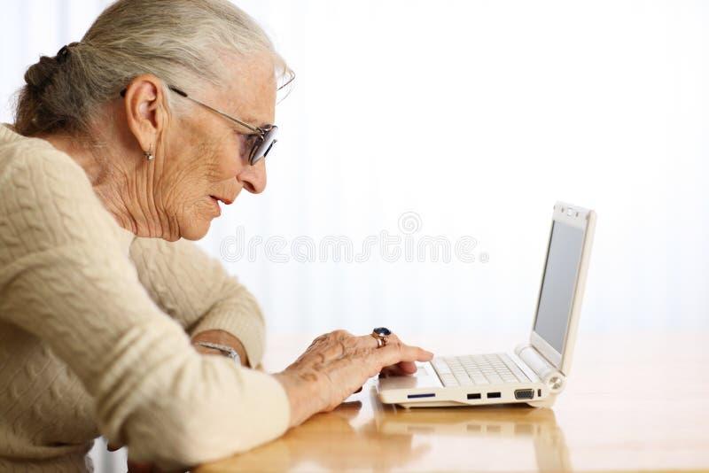Computador idoso da leitura da mulher imagens de stock
