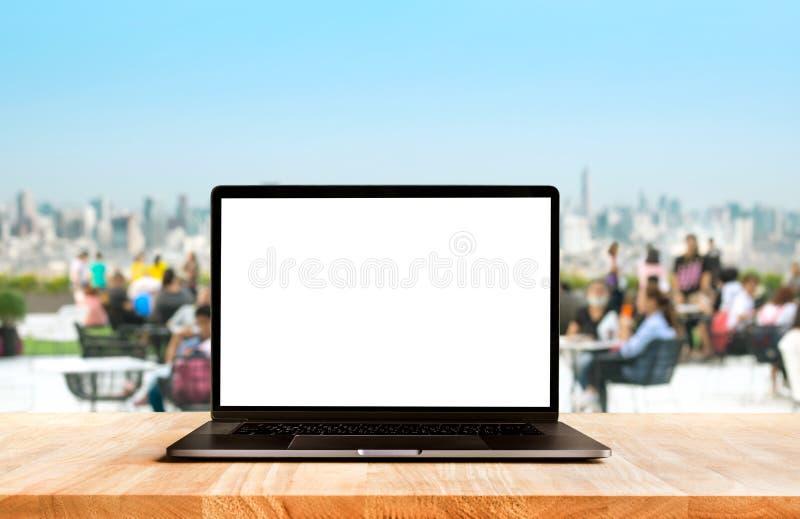Computador moderno, port?til com a tela vazia no caf? da tabela da mesa com fundos do parque de comunidade fotografia de stock