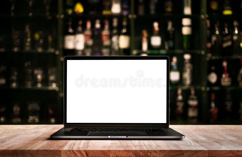 Computador moderno, portátil na barra contrária com a garrafa de vinho do borrão imagem de stock