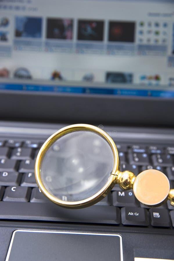 Computador portátil com lupa foto de stock
