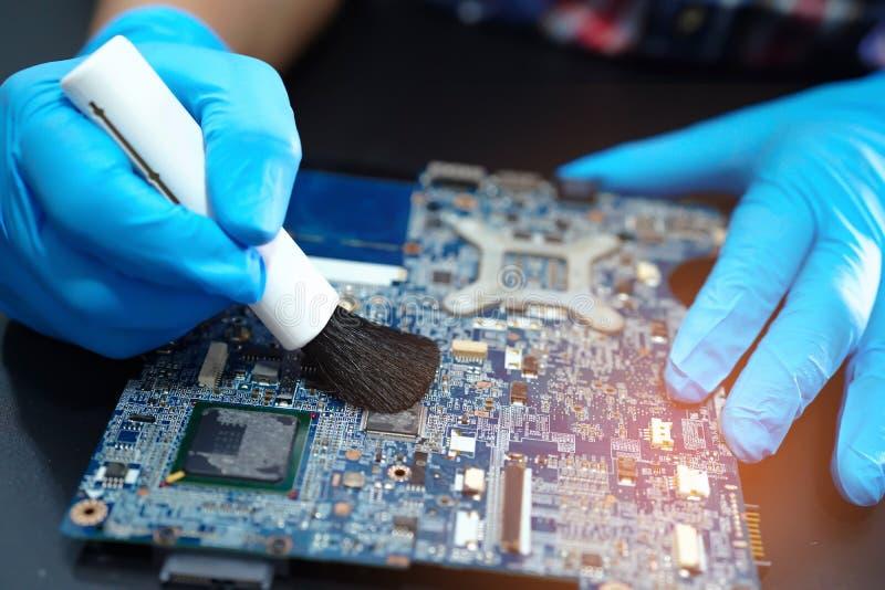 Computador sujo do prato principal do circuito asiático do reparo e da limpeza do técnico tecnologia eletrônica do micro com esco foto de stock