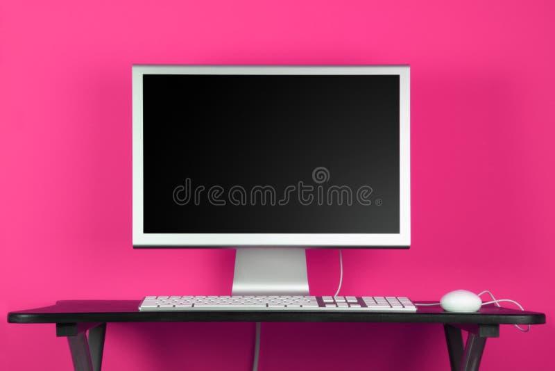 Computadora de escritorio y pared rosada imágenes de archivo libres de regalías