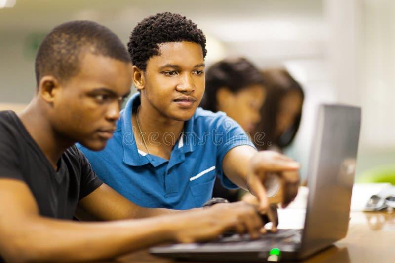 Computadora portátil africana de los estudiantes fotografía de archivo