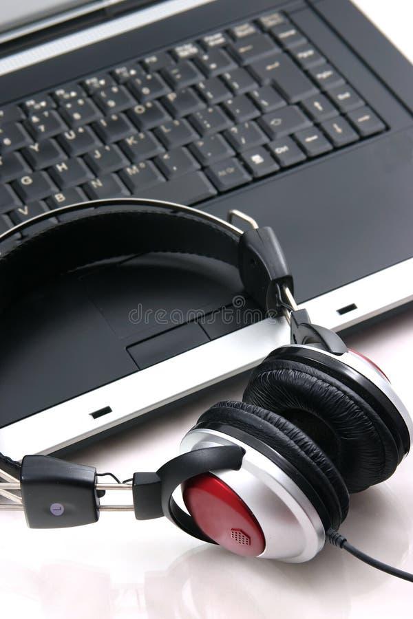 Computadora portátil, auriculares fotografía de archivo libre de regalías