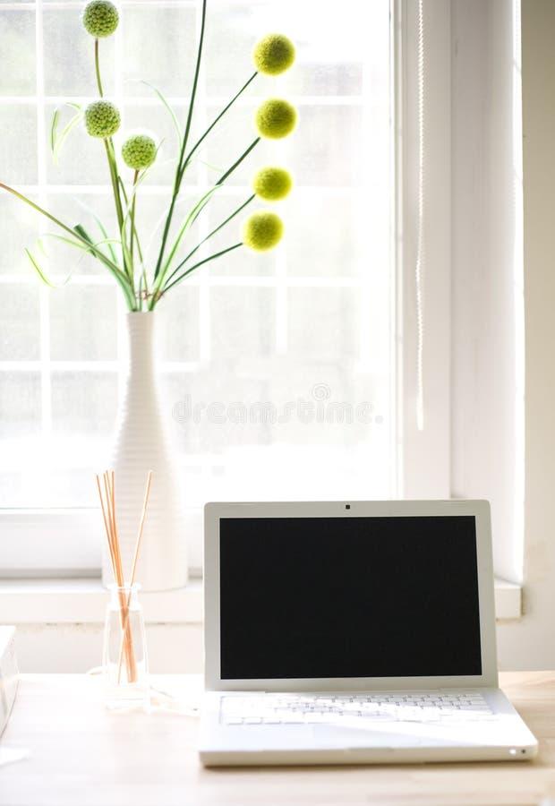 Computadora portátil blanca y un florero imágenes de archivo libres de regalías
