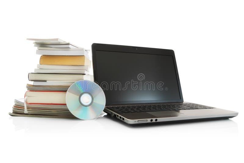 Computadora portátil, Cd, libros de la pila y compartimientos fotografía de archivo