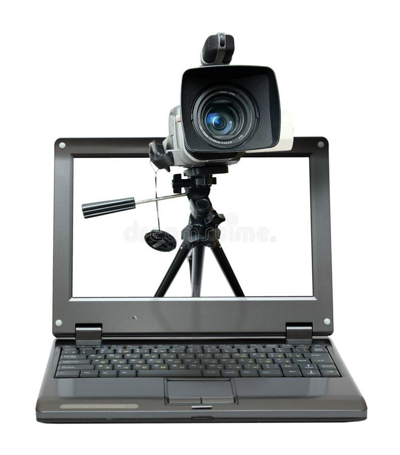 Computadora portátil con la cámara de vídeo en el trípode fotografía de archivo