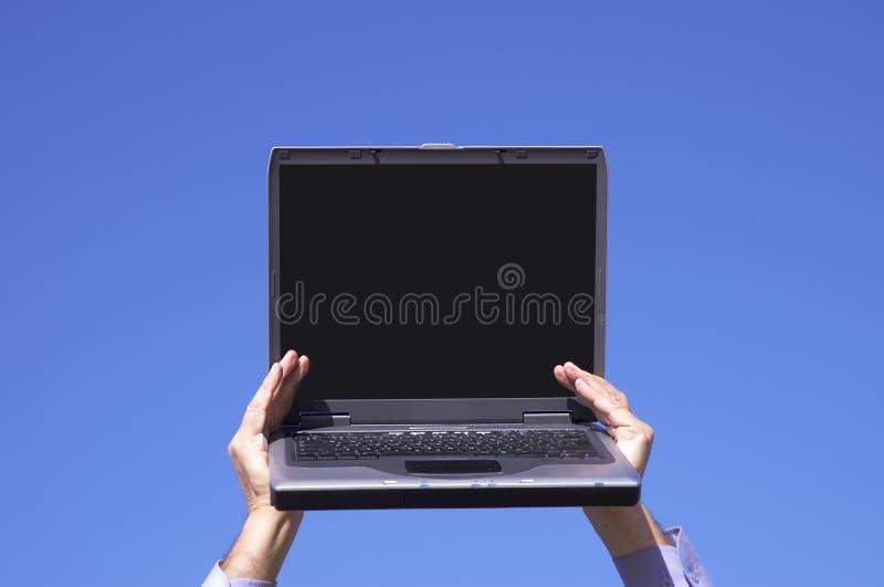 Computadora portátil con la pantalla vacía en manos imagen de archivo
