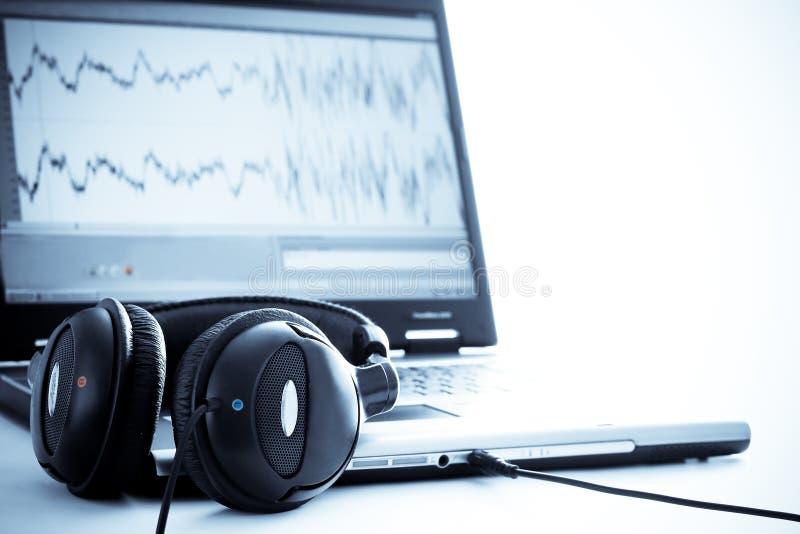 Computadora portátil con los auriculares foto de archivo libre de regalías