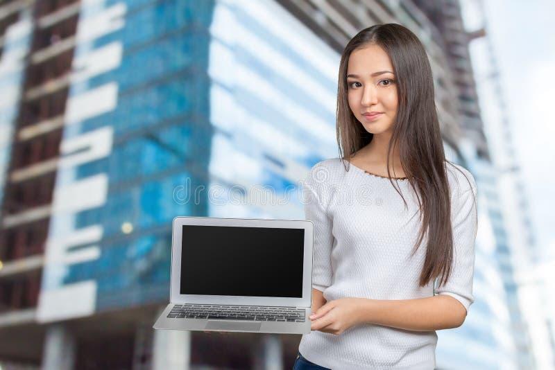 Computadora portátil de la explotación agrícola de la mujer joven fotos de archivo