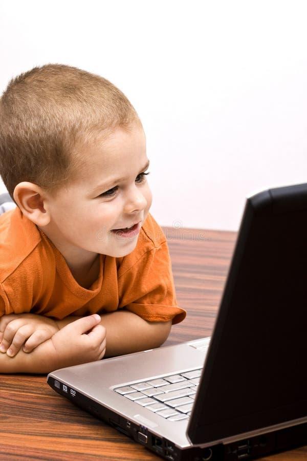 Computadora portátil de trabajo de la pizca del muchacho fotografía de archivo