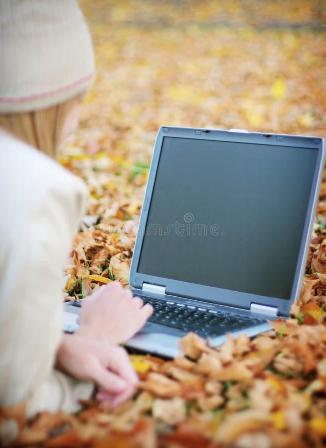 Computadora portátil del otoño de la mujer imagen de archivo libre de regalías