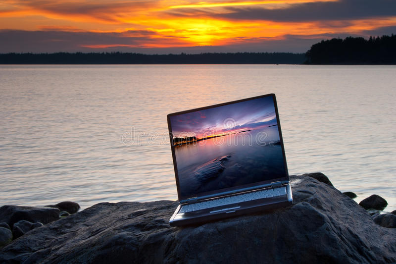Computadora portátil en la roca de la playa imagen de archivo libre de regalías