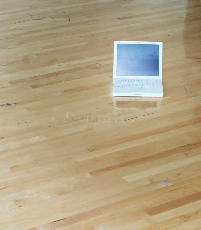 Computadora portátil en suelo de madera imagen de archivo