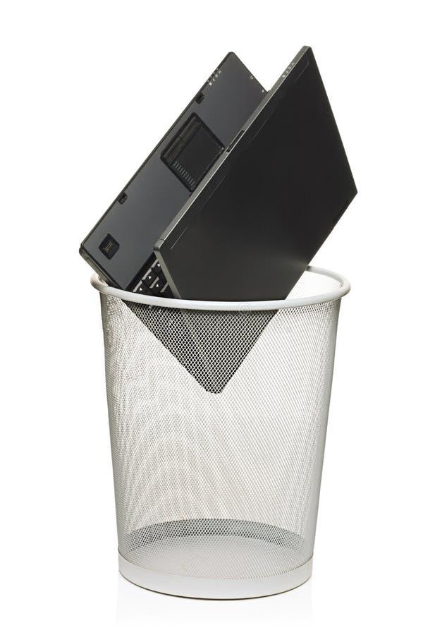Computadora portátil en un compartimiento de basura imagen de archivo