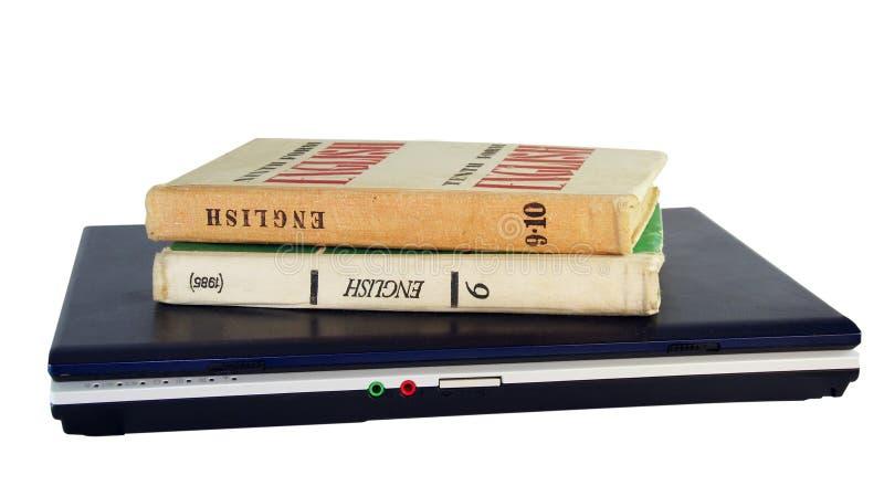 Computadora portátil y libro de textos foto de archivo libre de regalías