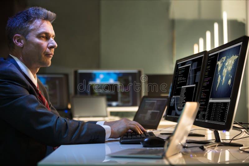 Computadores de Working On Multiple do homem de negócios imagens de stock