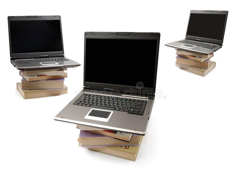 Computadores portáteis em pilhas dos livros