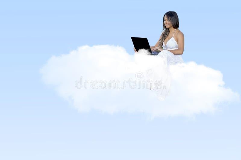 Computazione felice della nuvola della giovane donna fotografia stock