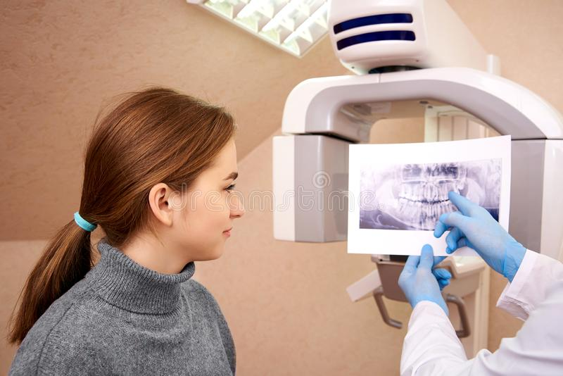 Computed tomography in dentistry. Dentist showing x-ray to her patient in dental clinic.Computed tomography in dentistry stock images