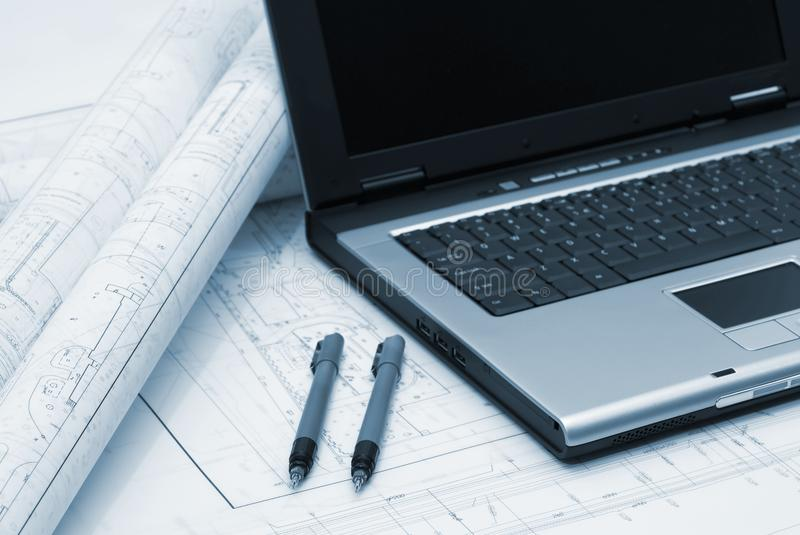 Computer and architectural plans in blue tint. Computer with architectural plans lying on table. Picture in blue tint stock image