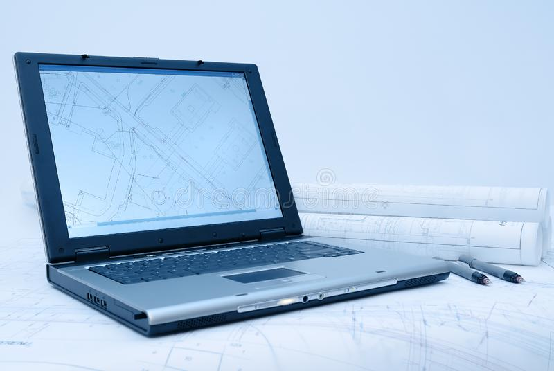 Computer and architectural plans in blue tint. Computer with architectural plans lying on table. Picture in blue tint royalty free stock photography