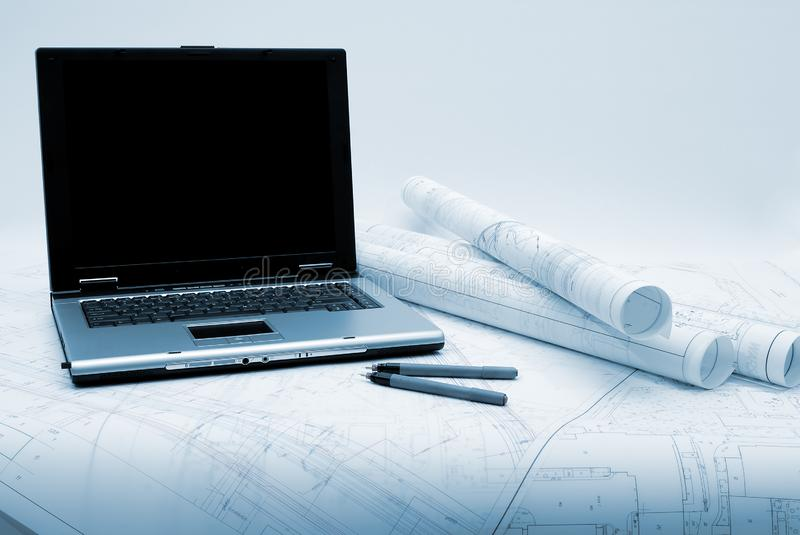Computer and architectural plans in blue tint. Computer with architectural plans lying on table. Picture in blue tint royalty free stock photo