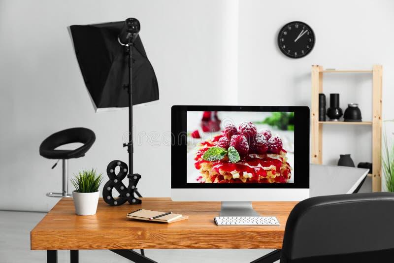 Computer auf Arbeitsplatz des Fotografen im modernen Studio stockfotografie